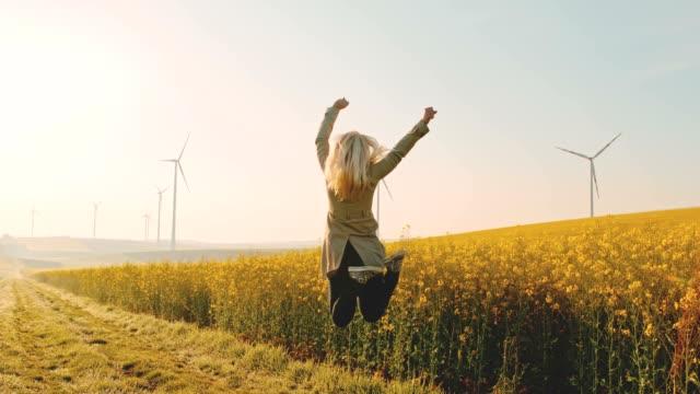 vídeos de stock, filmes e b-roll de super slo mo - time warp effect mulher pulando de alegria ao lado de um campo de canola com turbinas eólicas à distância - alegria