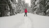 istock woman jumping  in the snowy forest 1199783055