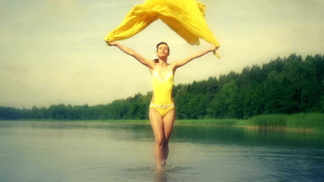 Woman jumping in water holding yellow scarf video