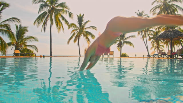 slo mo woman jumping into the pool of a luxury beach resort - palm tree filmów i materiałów b-roll