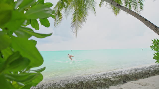 MS Woman jumping into tranquil tropical ocean,Maldives MS Woman jumping into tranquil tropical ocean,Maldives. Real Time. one mid adult woman only stock videos & royalty-free footage