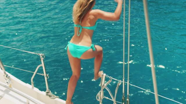 donna che salta in acqua - andare in barca a vela video stock e b–roll