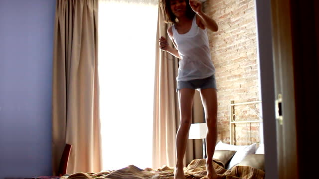 Woman jumping on bed, slow motion video