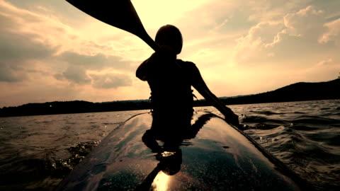 vídeos y material grabado en eventos de stock de kayak en un lago calmado durante la puesta de sol de mujer - actividades recreativas