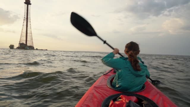 Woman kayaking to  lighthouse at sunset