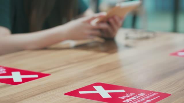 女性はcovid-19またはコロナウイルスを防ぐために座って距離を保つ - 飲食店点の映像素材/bロール