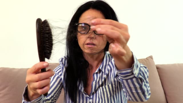 Woman keeping comb with hair in hand.Hair loss concept