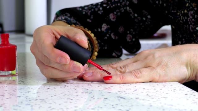stockvideo's en b-roll-footage met vrouw houden hand op tafel en het toepassen van nagellak - menselijke vinger