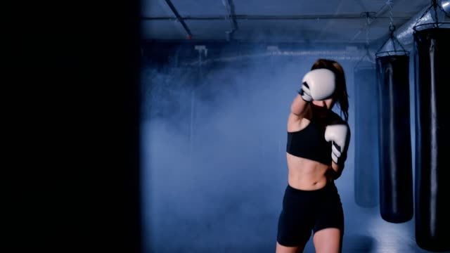 woman kickboxer shadow boxing as exercise for the fight - allenamento con l'ombra video stock e b–roll