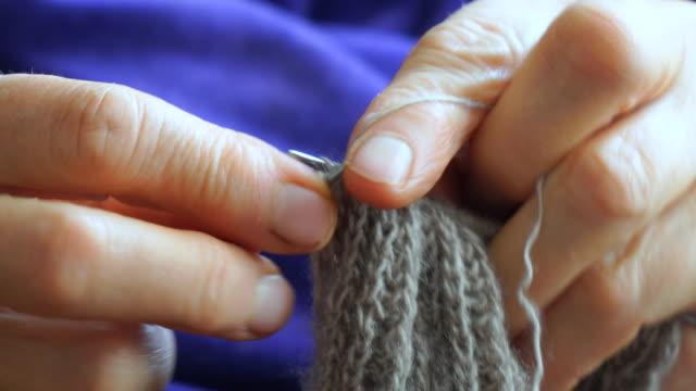 Woman knits sweater knitting needles
