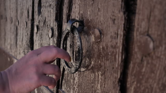 woman knocks on an old wooden door
