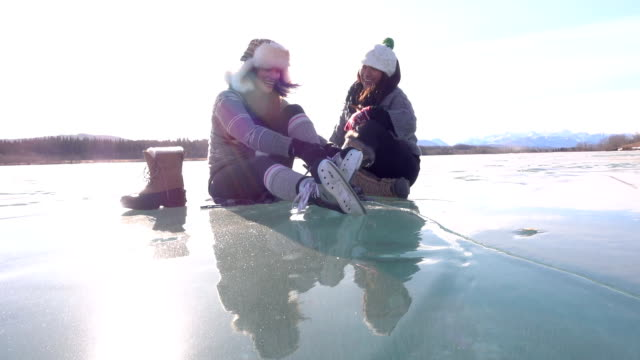 vídeos de stock e filmes b-roll de woman laces skates on frozen pond, with friend - skate liberdade gorro