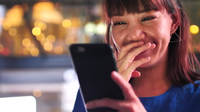 woman laughing and looking on mobile at night - espressione del viso video stock e b–roll