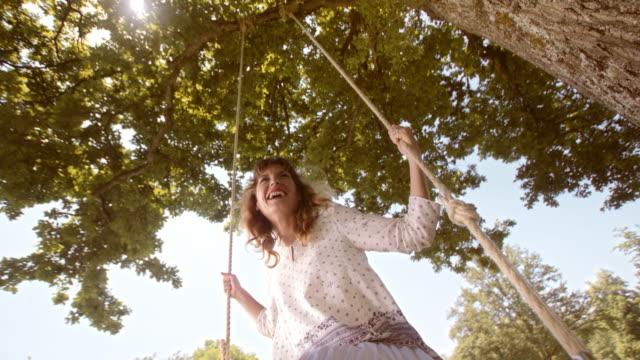 vídeos de stock e filmes b-roll de slo mo recipiente mulher rir em swing - 25 29 anos