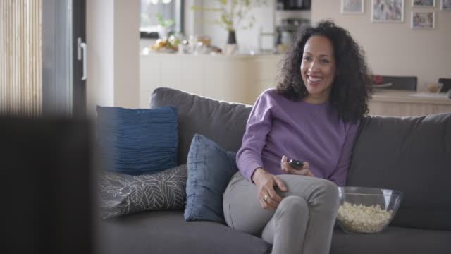 stockvideo's en b-roll-footage met vrouw lachen terwijl u tv kijkt op de bank - popcorn