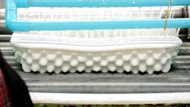 vídeos y material grabado en eventos de stock de mujer acostada almohada de látex blanco en la cinta transportadora para mover pasar a través del agua para la limpieza - colchón