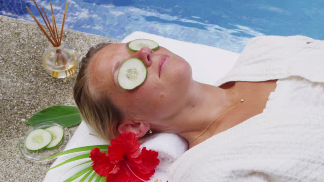 woman laying by pool at spa gets cucumbers on eyes. - cetriolo video stock e b–roll