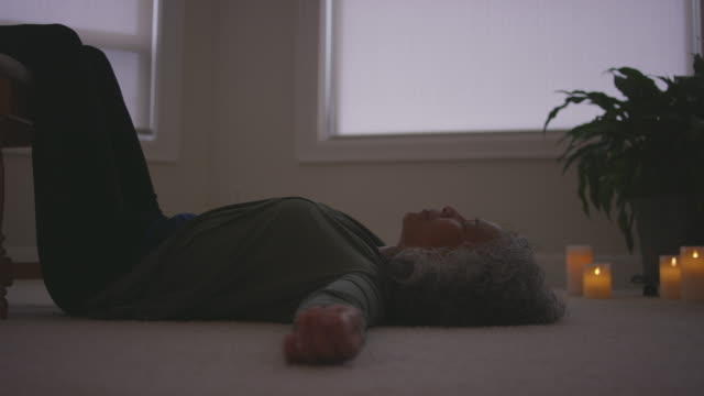woman laying on her back while meditating in her living room - mindfulness stock videos & royalty-free footage