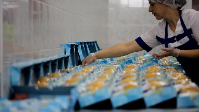 bir kadın gıda onboard bir yiyecek dükkanı kutulara ortaya konuyor - gıda ve i̇çecek sanayi stok videoları ve detay görüntü çekimi