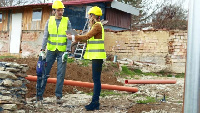 woman leader. a woman engineer giving orders to a construction worker using jackhammer. working on a construction site. drilling, construction site, construction industry, braking up a rock, - служащая стоковые видео и кадры b-roll