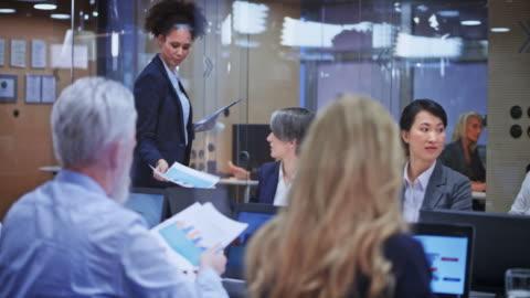 donna che conduce un incontro in sala conferenze - piano americano video stock e b–roll