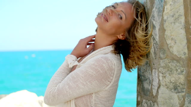 Woman Leaning Against Rock Wall By Windy Ocean video