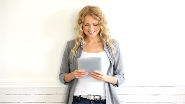 Woman leaning on wall with electronic tablet video