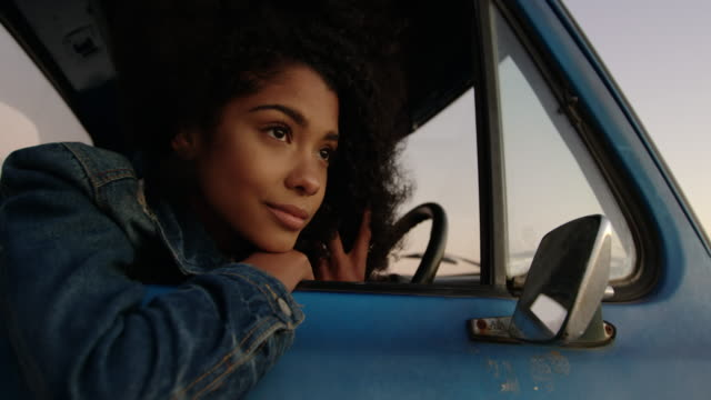Woman leaning on window of pickup truck at beach 4k Front view of African american woman leaning on window of pickup truck at beach. She is thoughtful and looking away 4k leaning stock videos & royalty-free footage