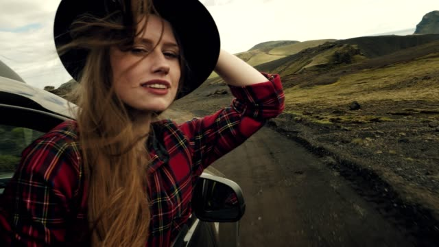 Woman leaning out of car window. On the road trip. Woman in black hat enjoying the journey leaning stock videos & royalty-free footage