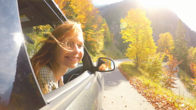 woman leaning out of car window while driving through autumn forest - spettinato video stock e b–roll