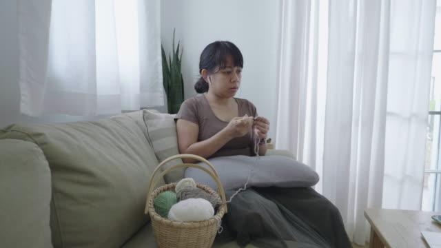 woman learning how to crochet online - auricolari wireless video stock e b–roll