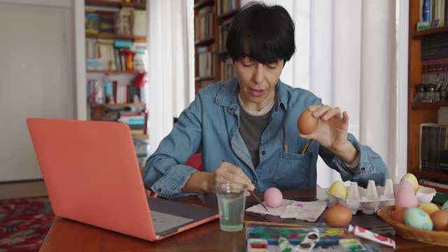 Woman learning how to decorate Easter eggs on laptop video call video