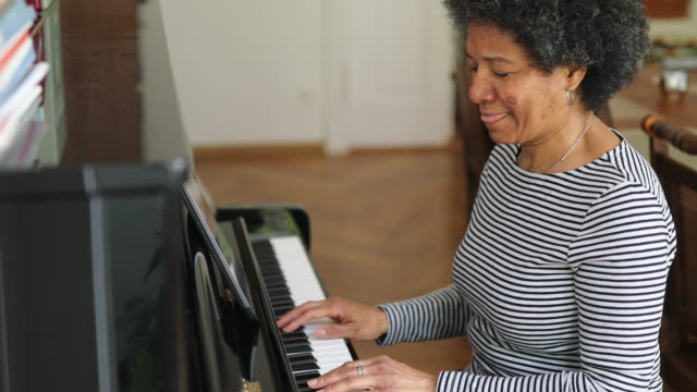 Woman learning playing piano at home during covid-19 pandemic