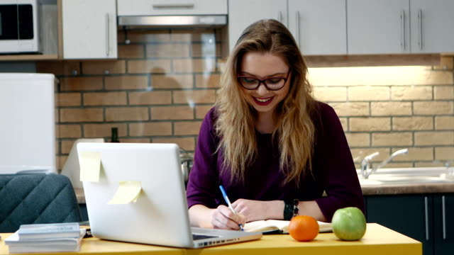 Woman learns on a computer and and writes notes in notepad in the kitchen at home.