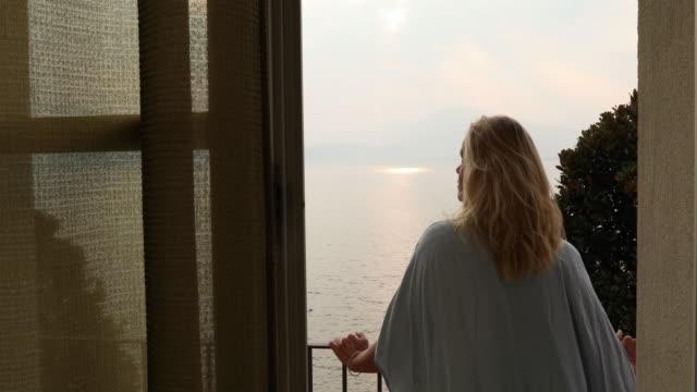 vídeos de stock e filmes b-roll de woman leaves doorway, walks onto veranda at sunrise - lago maggiore