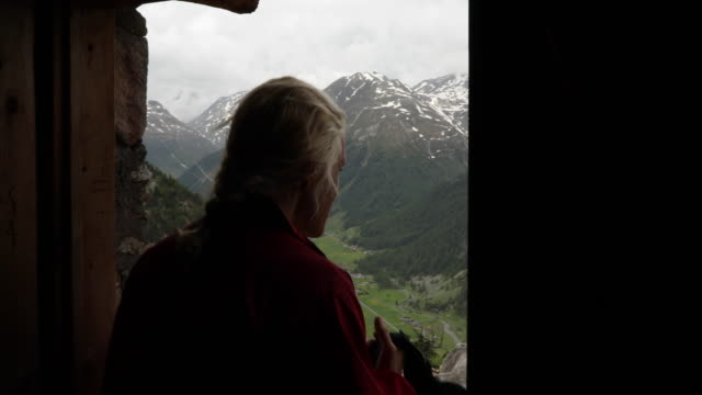 woman leaves mountain hut above valley below - livigno video stock e b–roll