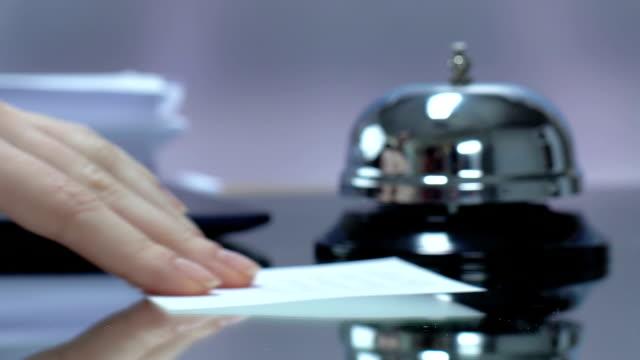 frau verlässt stück papier mit nachricht an der rezeption des hotels, nahaufnahme - weibliche angestellte stock-videos und b-roll-filmmaterial