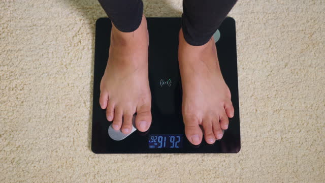 woman leg stepping standing on floor electric scales