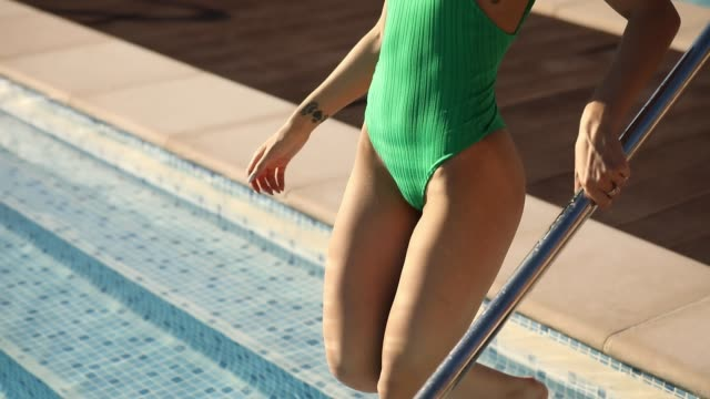 Woman legs go down to swimming pool video