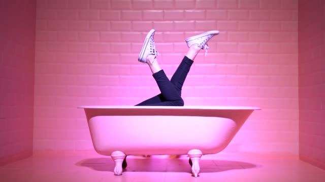 stockvideo's en b-roll-footage met vrouw benen having fun in de roze bad - surrealistisch
