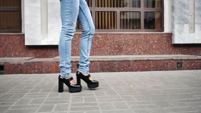 Woman legs in black platform shoes and blue jeans walking in the city street. video