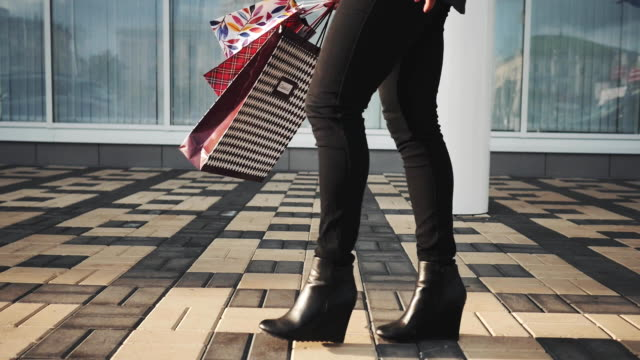 Woman legs in black shoes and jeans with Shopping Bags walking in the street video