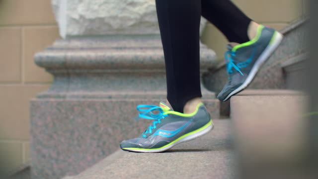 Woman legs in sport shoes walking down stairs. Legs in running shoes video