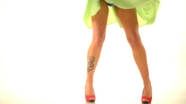vídeos de stock, filmes e b-roll de pernas de mulher com tatoo e salto alto em pontos brancos - saia