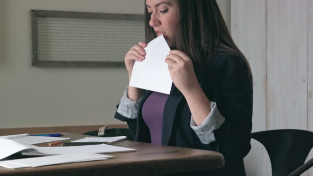 woman licks to seal envelope then writes address on letter - leccare video stock e b–roll