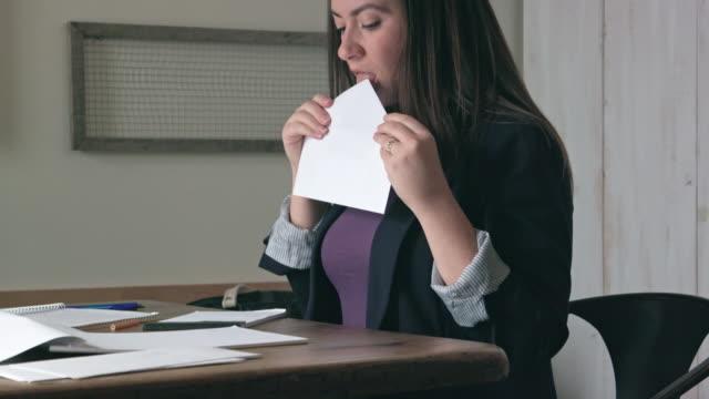 vídeos de stock e filmes b-roll de woman licks to seal envelope then writes address on letter - mensagem