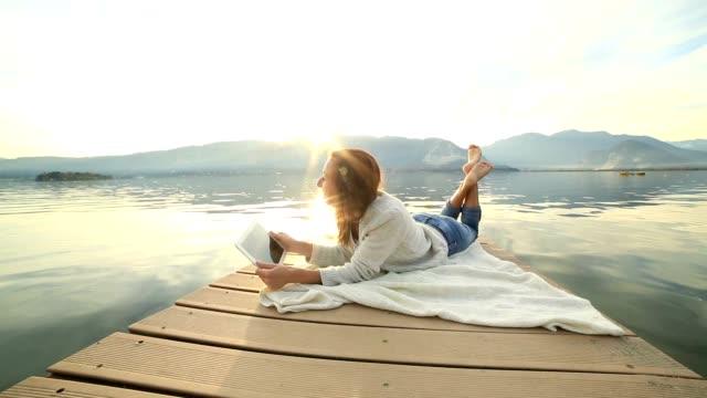 Woman lies on jetty using digital tablet video