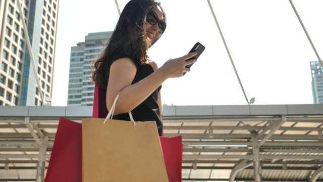 vídeos de stock e filmes b-roll de woman lifestyle with shopping bag and smart phone - online shopping