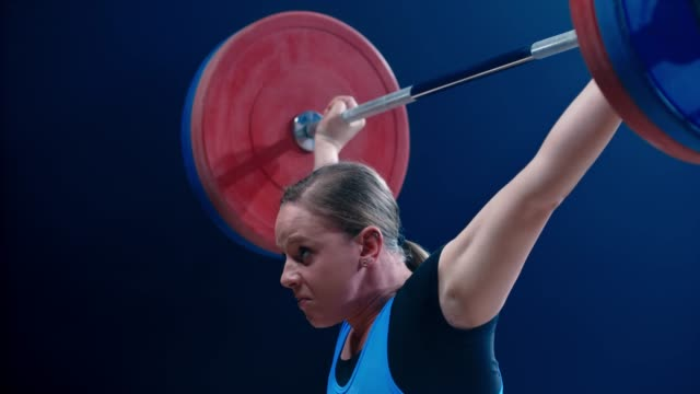 SLO MO TU Woman lifting a barbell above her head at a competition