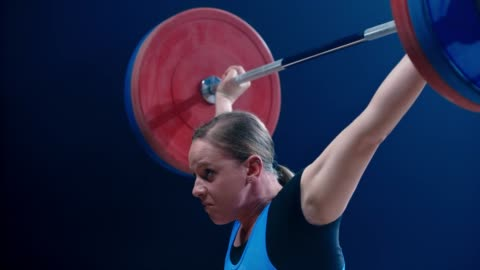 SLO MO TU Woman lifting a barbell above her head at a competition Slow motion medium tilt up shot of a female lifter performing the snatch at a competition. Shot in Slovenia. strength stock videos & royalty-free footage